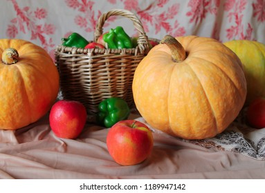 Autumn harvest. Fall still life with big yellow pumpkin, red apples and green pepper on the table. Vegetables in the basket.