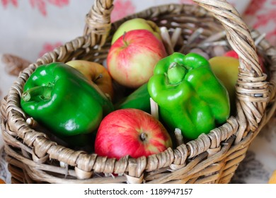 Autumn harvest. Fall still life with green pepper and red apples in the basket. Basket with fruits and vegetables.
