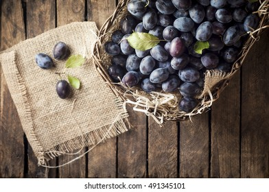 Autumn harvest - fresh plums in the basket on rustic wooden table. Three selected plums with a green leaf on a linen cloth outside the baskett. Copy space.  Top view
