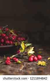 Autumn harvest Hawthorn berry with leaves in bowl on a wooden table background. Copy space. Dark rustic style. Natural remedy