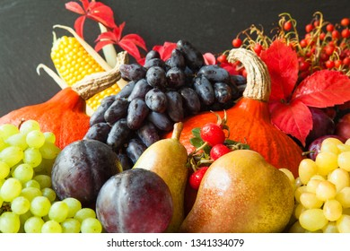 Autumn harvest: plenty of fresh fruits and vegetables on black background