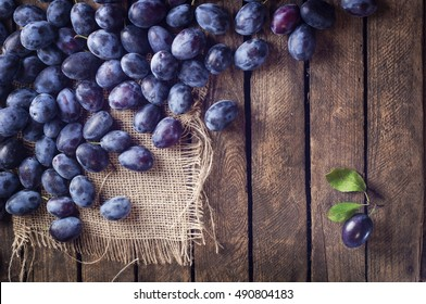 Autumn harvest. Plums on a rustic wooden background. Single plum with a green leaf. Perfect plum. Lonely in the crowd - concept image.