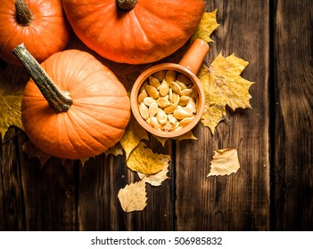 Autumn harvest. Pumpkin seeds with the maple leaves. On a wooden table.