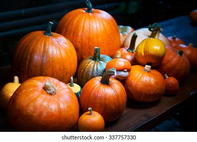 Autumn harvest. Pumpkins on table in garden at night. Focus on center.