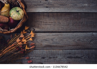 Autumn harvest pumpkins on vintage wooden background. Autumn composition with basket pumpkins, apples and flovers. Healthy organic vegetables. Thanksgiving organic food background with copy space.