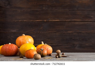 Autumn harvest pumpkins on wooden background. Autumn composition with pumpkins, apples pomegranate nuts and leaves Free space