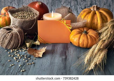 Autumn harvest still life with pumpkins, wheat ears and lentils in sack on faded blue rustic wooden background. Paper card with space for your text.
