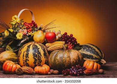 Autumn harvest of vegetables and flowers on the table. The composition of pumpins, corn, grapes, pears and apples.