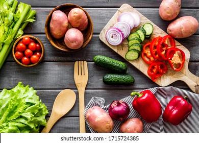 Herbsternte. Gemüse - Kartoffeln, Gurken, Mais, Grün - auf dunklem Holzhintergrund von oben nach unten