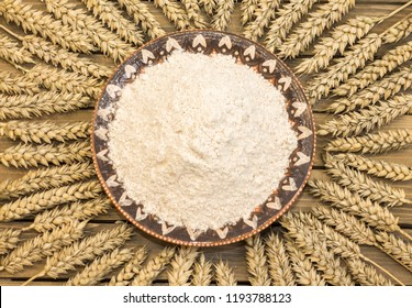 Autumn harvest of wheat or rye spikelets and flour on wooden background. Coarse grind flour in clay ornate ethnic plate with spikelets. Close up top view.
