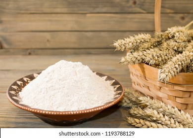 Autumn harvest of wheat or rye spikelets and flour on wooden background. Coarse grind flour in clay ornate ethnic plate with spikelets. Close up side view.