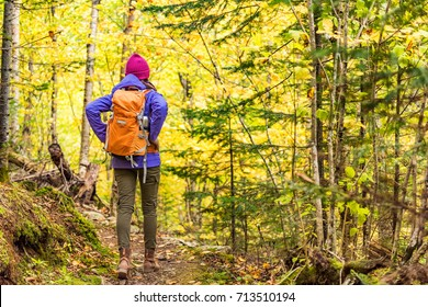 Autumn hike backpacker lifestyle woman walking on trek trail in forest outdoors with yellow leaves foliage. Fall outdoor activity girl with backpack and cold season gear hiking outside.