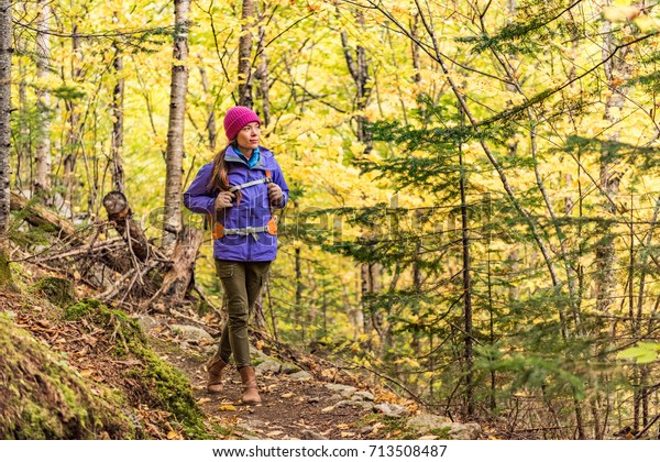Autumn hike backpacker lifestyle woman walking on trek trail in forest outdoors with yellow leaves foliage. Fall outdoor activity. Asian girl hiking outside with backpack and cold season camping gear.