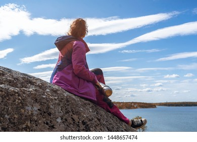 Autumn. Hiking. Girl traveler in violet jacket sitting on cliff and looking to horizon. Girl traveler holding a thermos in hands. Tourism. View of Scandinavia: rocky coast, Baltic sea, islands, pines