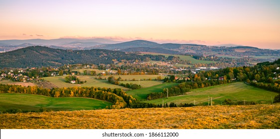 Autumn hilly landscape at sunset time. Colorful trees and meadows. View of Krkonose, Cisarsky kamen and Cerna Studnice, Czech Republic - Shutterstock ID 1866112000