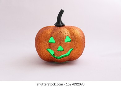 """Autumn holiday halloween. A plastic orange pumpkin with a """"sinister"""" grimace and a candle (multi-colored LEDs) inside, driving away evil spirits from the house. Pumpkin on a white background."""
