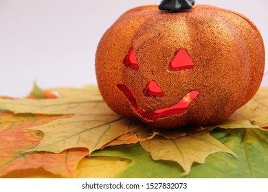 """Autumn holiday halloween. A plastic orange pumpkin with a """"sinister"""" grimace and a candle (multi-colored LEDs) inside, driving away evil spirits from the house.  Pumpkin on maple leaves."""