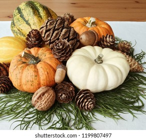 Autumn holiday house decorating: mini pumpkins of different colours, green branches, pine cones and acorns, white tablecloth, wooden rustic table top.
