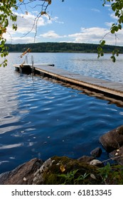 Autumn image of pier on lake in Finland. With colored leaves in foreground