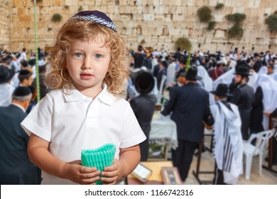 Autumn Jewish holiday Sukkot. People in white Taliths pray at the Western Wall of the Temple. Lovely blonde boy with blue eyes in a skullcap