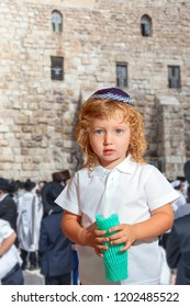 Autumn Jewish holiday Sukkot. Western Wall of the Temple, Jerusalem. Handsome little boy with blond side curls and blue eyes, in skullcap