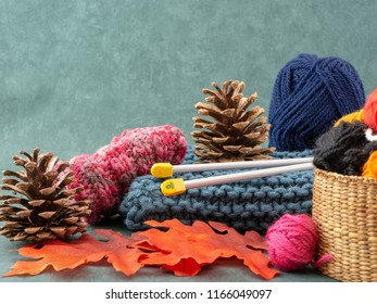 Autumn knitting image. Knitted items, a basket with balls of wool, autumn leaves, pine cones and knitting needles.  Front view fall knitting background.