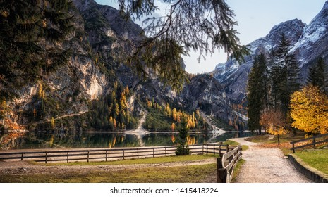 Autumn in Lago di Braies Park. Reflection of trees and clouds in lake.  South Tyrol. Italy. Europe. Main focus on wooden fence and path