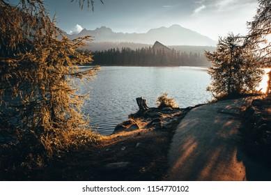 Autumn lakeside, beautiful sunrise and mountains. Treking, hiking photo, High Tatras, Slovakia