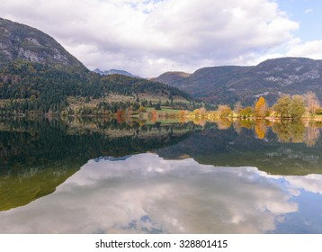 Autumn landscape by the lake Bohinj in Julian Alps. Fascinating reflectins in the lake on a cloudy day.