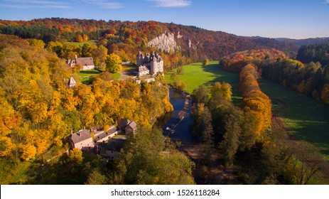 Autumn landscape with a castle by the river in Belgium