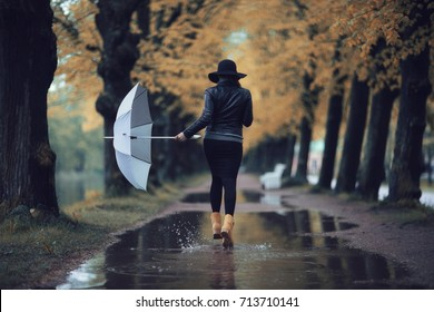 autumn landscape city woman umbrella rain puddles of yellow trees