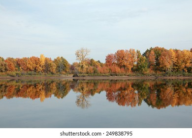 autumn landscape of colorful trees reflected in the mirrored surface of the calm river on a cloudy day