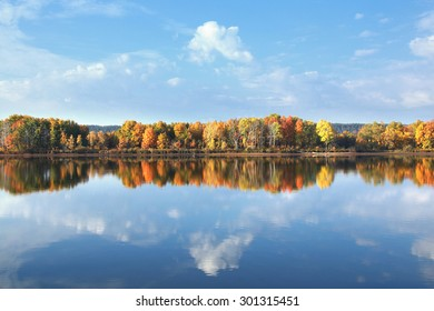 autumn landscape of colorful trees reflected in the mirrored surface of the calm river