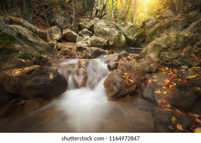 Autumn landscape. Composition of nature. Waterfall river into canyon.