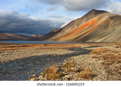 Autumn landscape with creek, lake and mountain. The slopes of the mountain are of unusual orange color. Clouds in the sky. September in the far north. Iskaten Ridge, Chukotka, Far East of Russia.