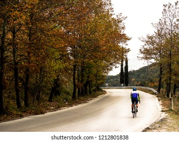 Autumn landscape and cycler on bicycle on the road