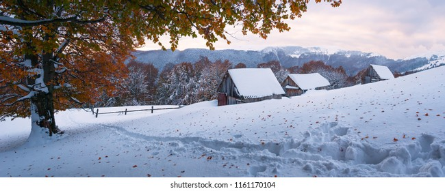 Autumn landscape with the first unexpected snow. Old wooden shepherds huts on a mountain hill. Snowy trail