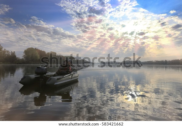 autumn landscape fisherman in an inflatable boat in the early morning on the river