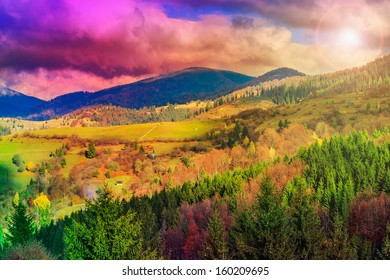 autumn landscape. forest on the hillside covered with red and yellow leaves. over the mountains the beam of light falls on a clearing at the top of the hill.