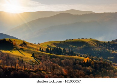 autumn landscape. forest on a hillside covered with red and yellow leaves. over the mountains