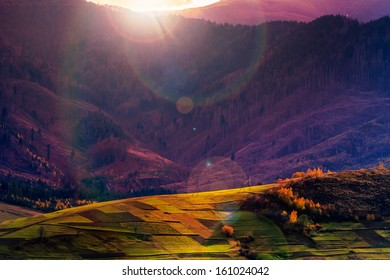 autumn landscape. forest on a hillside covered with red and yellow leaves. over the mountains in evening