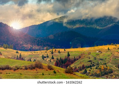 autumn landscape. forest on a hillside covered with red and yellow leaves. over the mountains in clouds