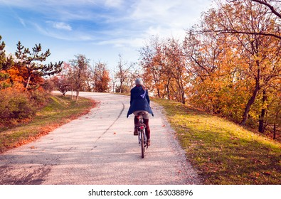 Autumn landscape. Girl cycling up to the mountain.