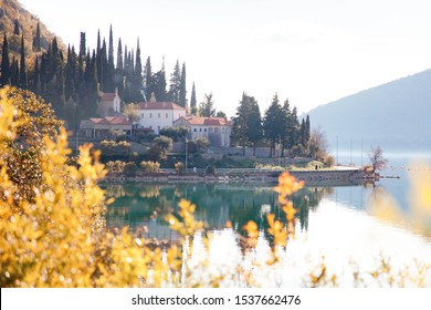 Autumn landscape. House on coastline with mountains, fall leaves, sea. Yellow and orange tree near blue water. Ancient monastery Risan, The Kotor Bay, Montenegro.