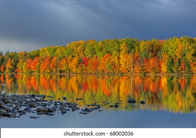 Autumn landscape of Moccasin Lake with reflections of trees in calm water and storm clouds, Michigan's Upper Peninsula, USA