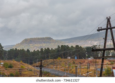 Autumn landscape with mountains in fog and yellow grass and electrical poles on the foreground. Special photographic vision of focus and horizon.