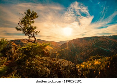 Autumn landscape in national park, Russia, Siberia. View of the mountains and valley, sunset, soft focus.