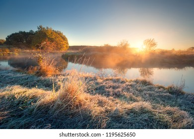Autumn landscape. Autumn nature. Sunny frosty autumn morning. Grass with frost at the riverside. Mist over river. Sun with sunrays shines through mist. Fall outdoors background.