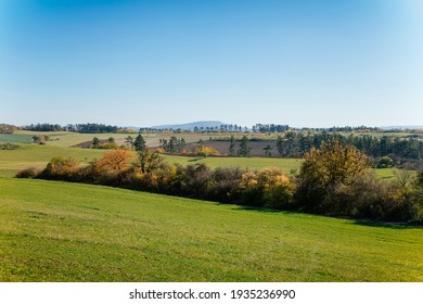 Autumn landscape near royal castle Tocnik, sunny day, Red and yellow leaves on trees, green fields and lawns, fresh green grass, the pasture, blue cloudless sky, hills on the horizon, Czech Republic