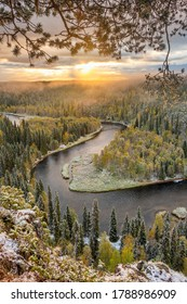 Autumn landscape in Oulanka National Park at sunrise in Finland. Beautiful river in pine forest in Northern Finland. Forest covered with first snow